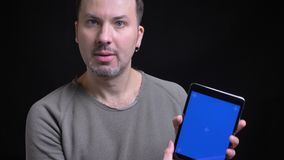 Middle-aged concentrated caucasian man with earring watching seriously into tablet shows its blue screen into camera on. Black background stock footage