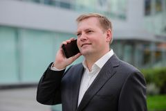Middle aged confident businessman, talking on the phone, outside. Portrait of middle aged confident businessman at the office, outside. Smiling Stock Images