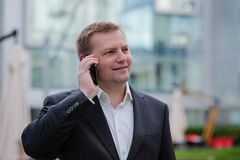 Middle aged confident businessman, talking on the phone, outside. Portrait of middle aged confident businessman at the office, outside. Smiling Royalty Free Stock Image