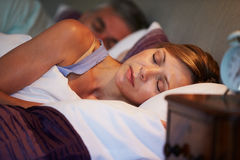 Middle Aged Couple Asleep In Bed Together. Lying Down Royalty Free Stock Photo