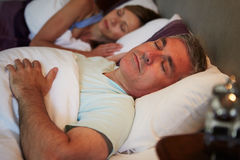 Middle Aged Couple Asleep In Bed Together. Middle Aged Couple Lying Down Asleep In Bed Together Stock Image