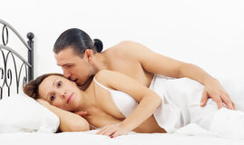 Middle-aged couple awaking in bed Stock Images