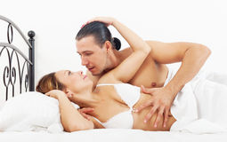Middle-aged couple awaking together in bed stock image