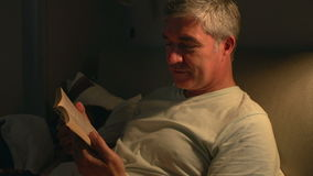 Middle Aged Couple In Bed With Man Reading Book stock footage