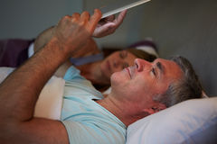 Middle Aged Couple In Bed With Man Using Tablet Computer Stock Image