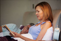 Middle Aged Couple In Bed Together With Woman Reading Book Royalty Free Stock Images