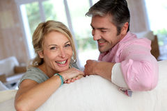 Middle-aged couple being happy relaxing on sofa Stock Photos
