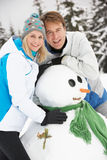 Middle Aged Couple Building Snowman On Ski Holiday Royalty Free Stock Photos