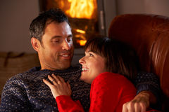 Middle Aged Couple Chatting By Cosy Log Fire. Middle Aged Couple Chatting On Sofa By Cosy Log Fire on winter vacation Royalty Free Stock Images
