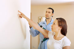 Middle-aged couple choosing point for hole in  wall Royalty Free Stock Photography