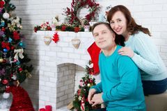 Middle aged couple in the christmas room, New Year`s fireplace and Christmas tree, loving family stock image