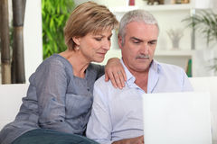 Middle-aged couple with a computer Stock Images