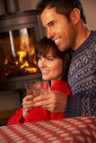 Middle Aged Couple By Cosy Log Fire With Drinks. Middle Aged Couple Sitting On Sofa Watching TV By Cosy Log Fire Royalty Free Stock Photography