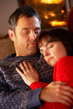 Middle Aged Couple Cuddling By Cosy Log Fire Royalty Free Stock Images