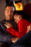 Middle Aged Couple Cuddling On Sofa. By Cosy Log Fire falling asleep on winter vacation Royalty Free Stock Photo