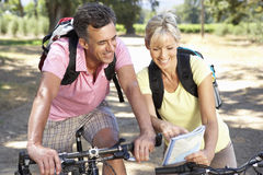 Middle Aged Couple Cycling Through Countryside Stock Image