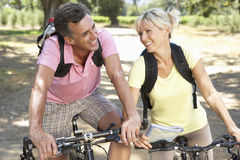 Middle Aged Couple Cycling Through Countryside Royalty Free Stock Image