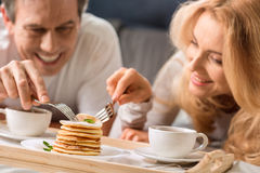 Middle aged couple eating pancakes together in bed Stock Photography
