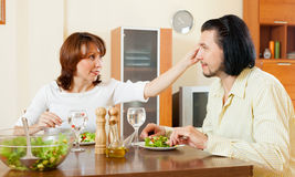 Middle aged couple eating salad with water at home. Stock Photo