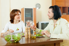 Middle aged couple eating vegetarian salad with clean water at h. Happy middle aged couple eating vegetarian salad with clean water at home Royalty Free Stock Photography