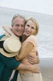 Middle-aged couple embracing on beach and looking at camera Royalty Free Stock Photos