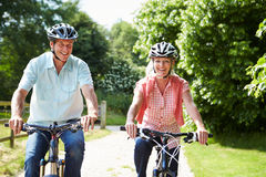 Middle Aged Couple Enjoying Country Cycle Ride Together. Wearing Helmets Smiling Stock Image
