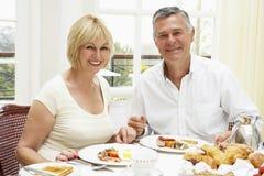 Middle Aged Couple Enjoying Hotel Breakfast. Smiling at camera stock image