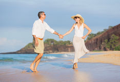 Middle Aged Couple Enjoying Walk on the Beach Stock Photo