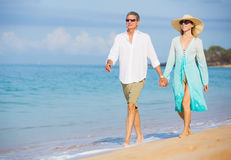 Middle Aged Couple Enjoying Walk on the Beach. Happy Romantic Middle Aged Couple Enjoying Walk on the Beach, Vacation Retirement Concept Stock Images