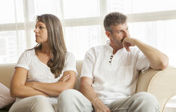 Middle aged couple fighting. Middle aged couple at home on the sofa and fighting stock images