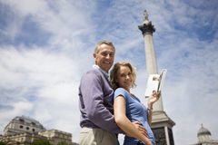 A middle-aged couple in front of Nelson's column, holding a guidebook Royalty Free Stock Image