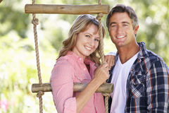 Middle Aged Couple In Garden By Treehouse Stock Photos