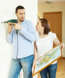 Middle-aged  couple hanging the  picture. On wall at home Royalty Free Stock Photography