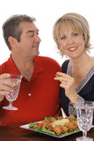 Middle aged couple having appetizers vertical. Isolated on white Royalty Free Stock Photos