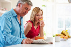 Middle Aged Couple Having Breakfast In Kitchen Together Stock Image