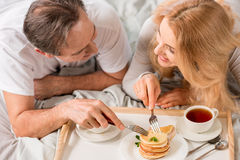 Middle aged couple having breakfast together in bed Royalty Free Stock Photos