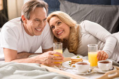 Middle aged couple having breakfast together in bed Royalty Free Stock Images