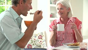 Middle Aged Couple Having Breakfast Together In Kitchen stock footage