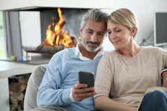 Middle-aged couple having fun on smartphone Stock Photos