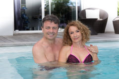 Middle aged couple Having Fun In Swimming Pool Stock Photos