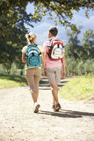 Middle Aged Couple Hiking Through Countryside Viewed From Behind Stock Image