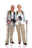 Middle aged couple hiking. Happy middle aged couple hiking isolated on white royalty free stock image