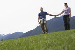 Middle Aged Couple Holding Hands On Meadow Royalty Free Stock Image