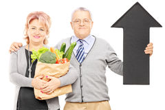Middle aged couple holding a paper bag full of groceries and big. Black arrow pointing down isolated on white background Royalty Free Stock Photo