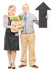 Middle aged couple holding a paper bag full of groceries and big. Full length portrait of a middle aged couple holding a paper bag full of groceries and big Stock Image