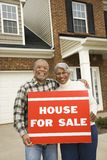 Middle-aged couple holding a for sale sign. Portrait of middle-aged African-American couple outside house with for sale sign Stock Photos