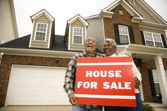 Middle-aged couple holding a for sale sign. Portrait of middle-aged African-American couple outside house with for sale sign Stock Images