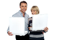 Middle aged couple holding white pizza boxes Stock Photos