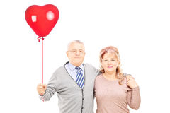 Middle aged couple in hug holding a red heart balloon Stock Photos