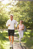 Middle Aged Couple Jogging In Park Royalty Free Stock Photography
